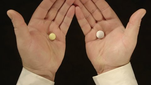 Last chance to guess which hand. Ta-daaaa! It's here! Man holding a pills in different colors offering to guess which hand