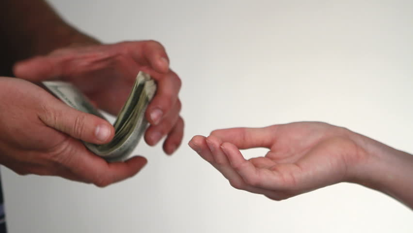 Close up of paying cash from man's hands counting out one hundred dollar bills into a woman's hand.