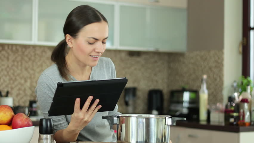 Young woman cooking with help of recipe on tablet computer