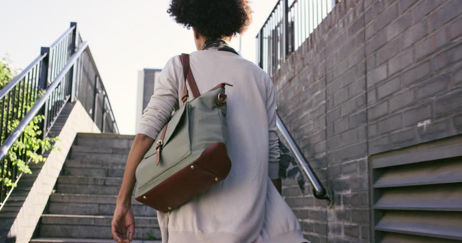 Beautiful Mixed race woman walking through urban city streets fashion lifestyle
