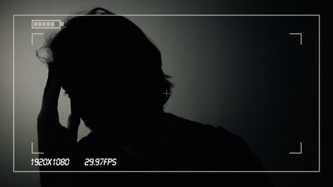 Person in witness protection program during police interview recorded on camera, silhouette of male giving statement to the police detectives during crime interrogation in dark room.