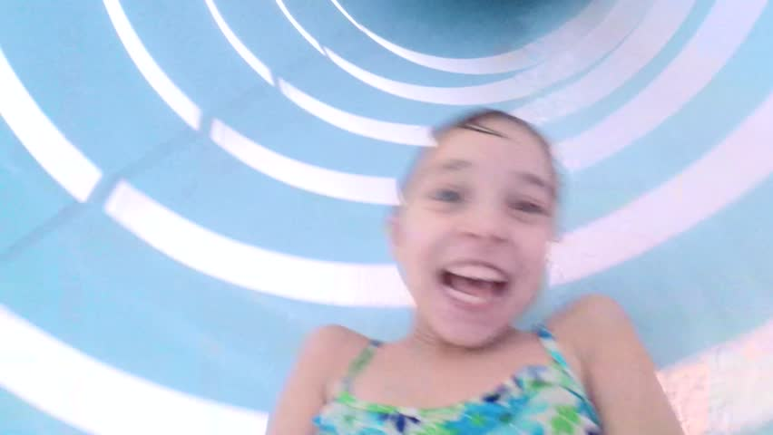 Happy little girl has into pool after going down water slide during at aqua park