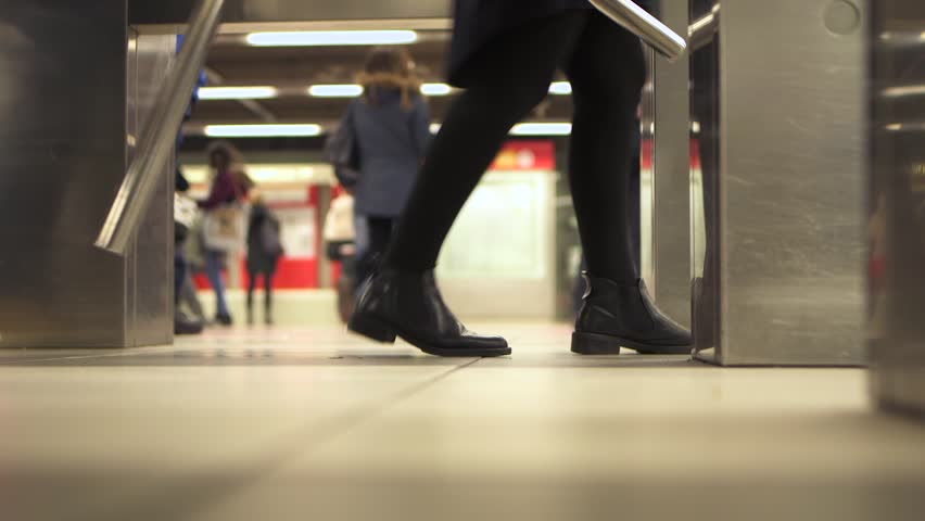 People pass through the turnstiles in the subway in rush hour