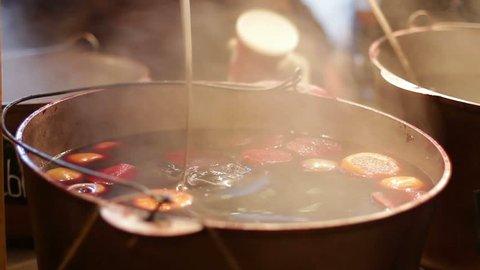 Mulled wine in saucepan. Hot drink. Fruit drink. Food fair. Eating fast food. Street food.