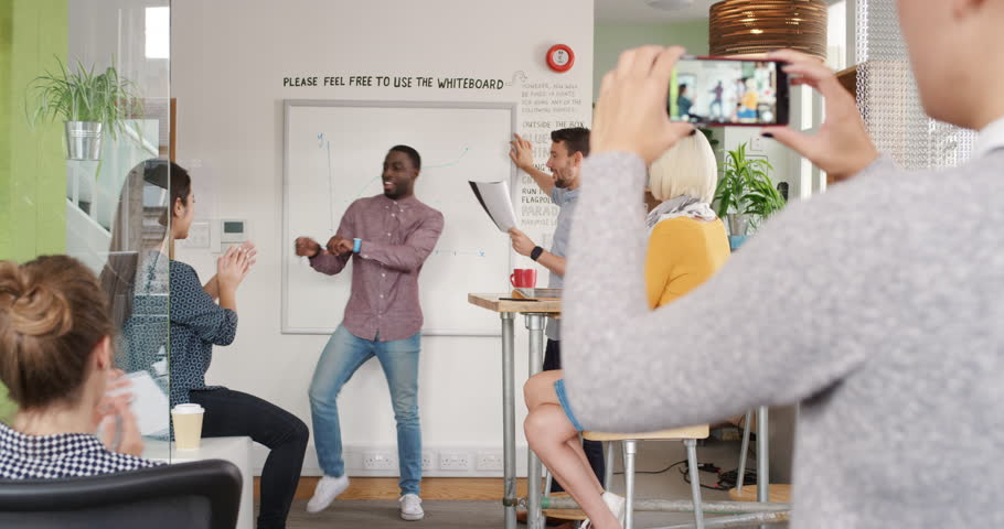 Crazy happy businessman dancing doing victory dance in team meeting celebrating success achievement | Shutterstock HD Video #13948802