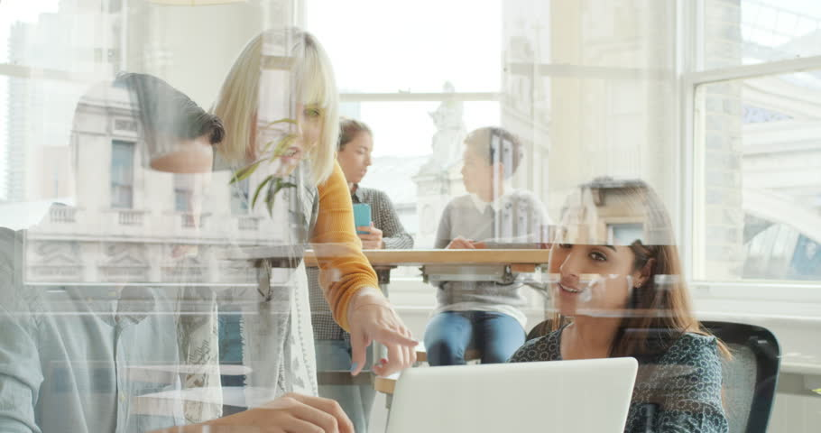 Creative business team meeting in modern start up office female team leader pointing at screen discussing diverse people group teamwork using digital display technology | Shutterstock HD Video #13949594