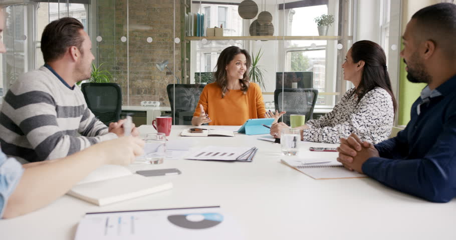 Diverse business people clapping in Creative team meeting celebrating success in casual modern office boardroom with natural light and large open windows | Shutterstock HD Video #13949990