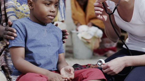 A medical worker from a charity organization lets a little boy use her stethoscope to listen to her heartbeat. In slow motion.