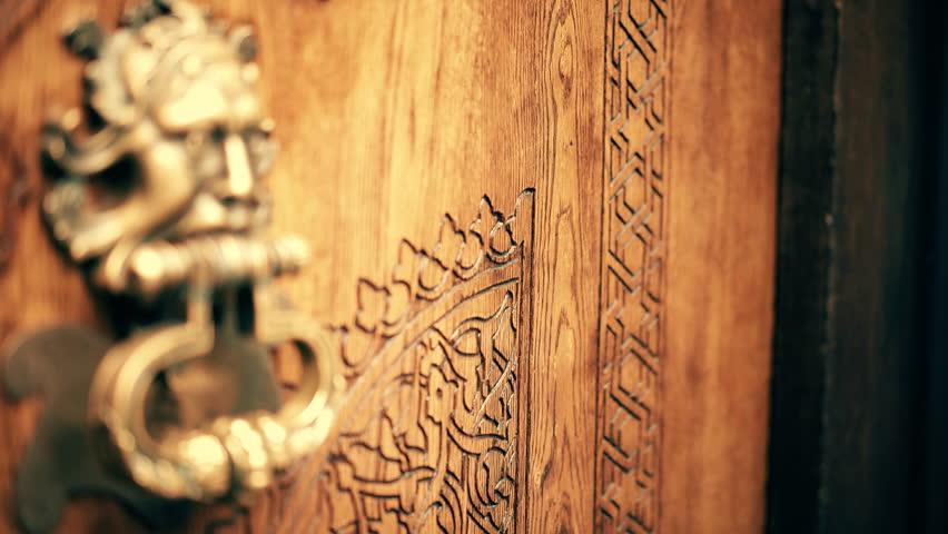 Focus pull over ancient wooden door on hand knocker. Hand opens doors. Wooden carved door with bronze hand knocker. UHD