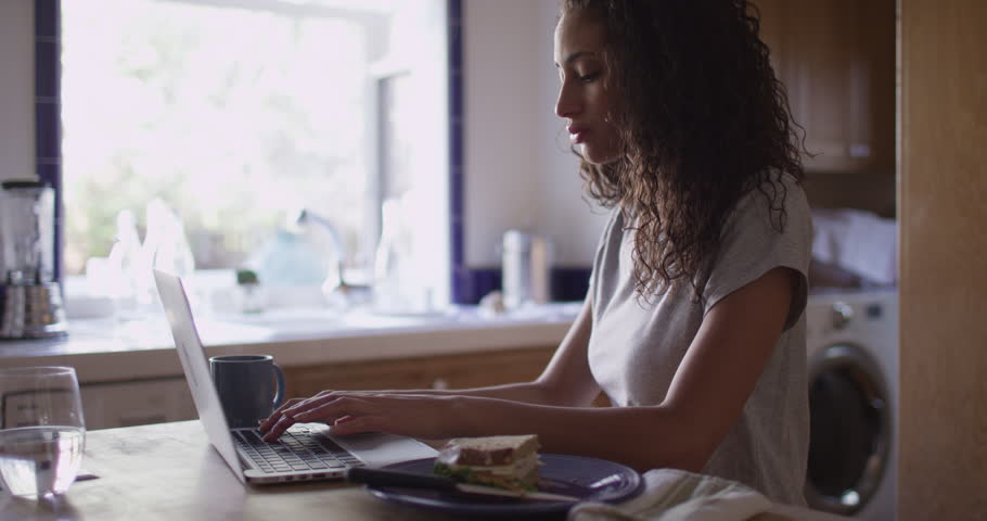 Pretty hispanic woman typing on a laptop computer in kitchen | Shutterstock HD Video #13972859