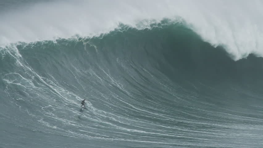 NAZARE, PORTUGAL - NOVEMBER 1, 2015: Big wave surfers ride huge waves. Nazare, an iconic surfing spot, is the home to some of the largest waves on earth.