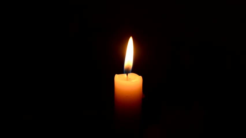lighting candle match on black/single candle burning on dark