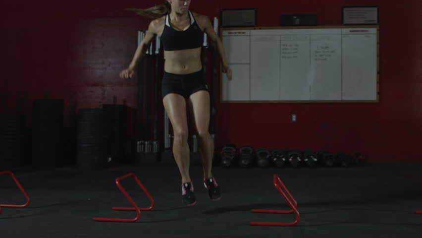 Dolly medium wide shot of a young woman jumping side to side over mini hurdles doing an exercise in a gym in slow motion - fitness / crossfit / workout