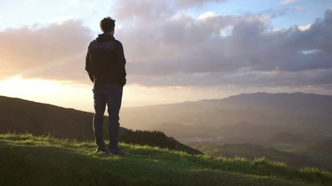 Young caucasian man looking down from the mountaine towards the ocean