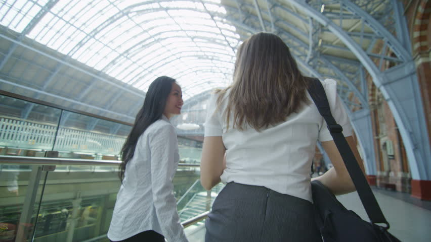 4k / Ultra HD version Attractive female friends or business colleagues chat together as they walk through St. Pancras railway station in London. In slow motion. Shot on RED Epic   Shutterstock HD Video #13999049