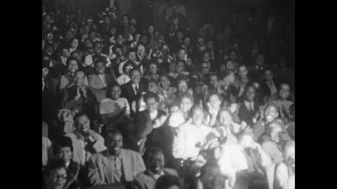 Spotlight panning audience in theater from right to left, 1950s