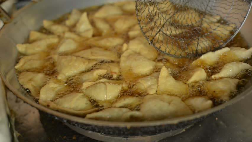 Samosa being fried in bowl with oil,Indian food