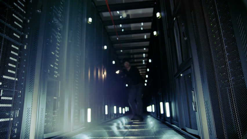 4k / Ultra HD version A suspicious man dressed all in black has broken into a data center and is prowling the corridors with a flashlight. Shot on RED Epic | Shutterstock HD Video #14049989