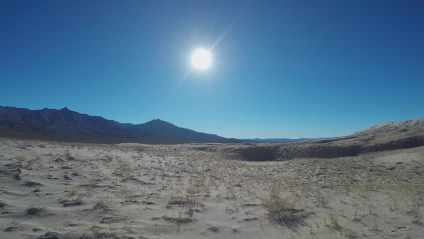 KELSO, CA/USA - January 15, 2016: Slow zoom in shot of the Mojave Desert sand dunes and mountains under a clear and bright sun. Clip conveys a beckoning into the mysterious unknown.