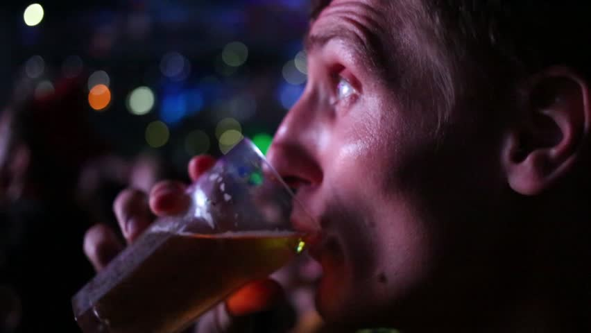 Young man drinks beer among other people in night club