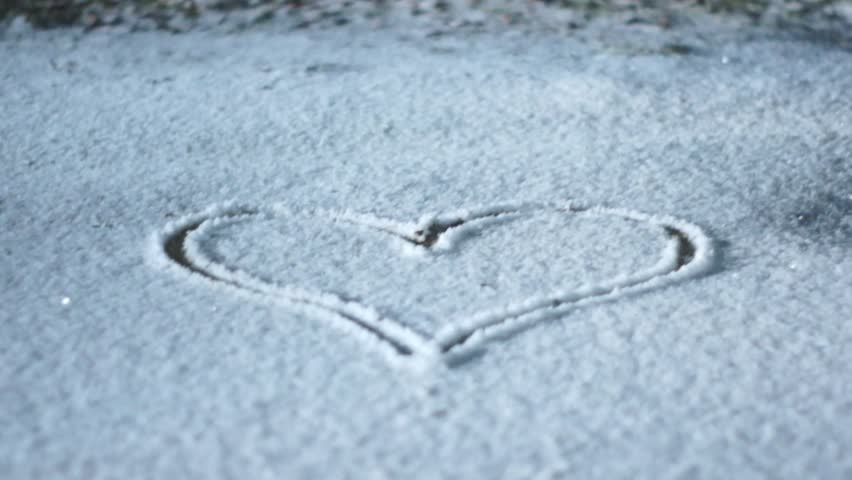 Heart drawing in the snow. Slowly moving camera.   Shutterstock HD Video #14073119