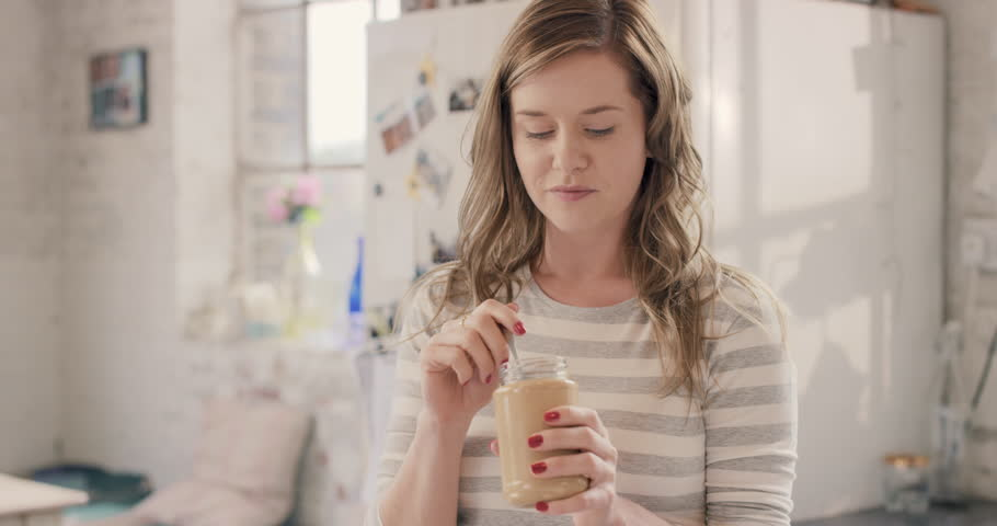 Pretty girl cheeky face eating peanut butter from jar using spoon wearing pajamas at home by window