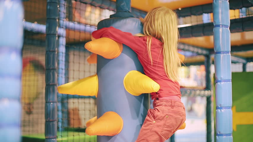 Small girl playing in children's playroom. A lot of colorful equipment are in the indoor playground. | Shutterstock HD Video #14096609