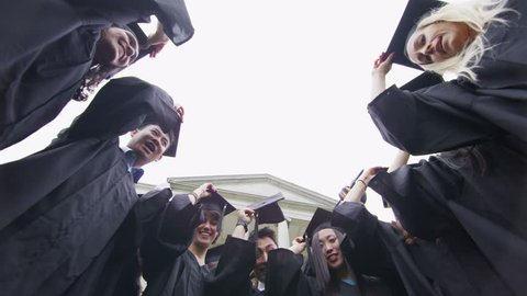 Happy and excited group of student friends on graduation day throw their caps into the air from the balcony of historic university building. In slow motion.