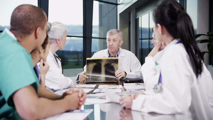 4k / Ultra HD version A diverse team of medical personnel are having a meeting in a light, modern private healthcare facility. They are discussing x-rays and looking for a diagnosis. In slow motion.  | Shutterstock HD Video #14127464