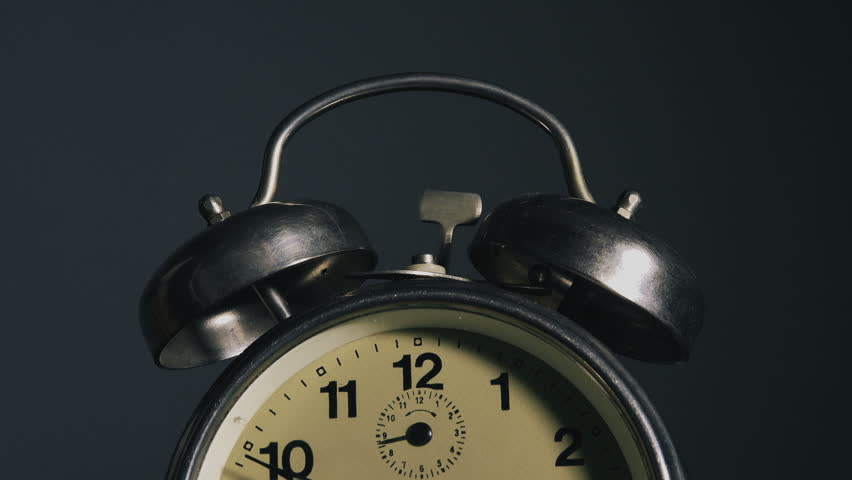 Vintage alarm clock ringing, clock face detail with ringing bells.