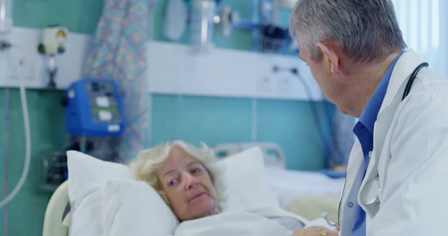4k / Ultra HD version Male doctor chatting with a female patient in hospital and discussing the results of her x ray. Shot on RED Epic #14148029