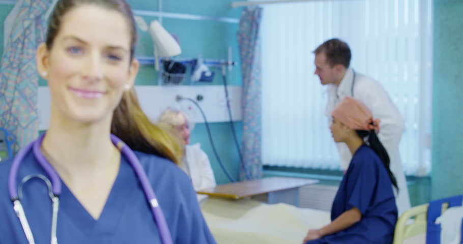 4k / Ultra HD version Portrait of smiling female doctor on a hospital ward with other medical staff working and taking care of patients in the background. In slow motion. Shot on RED Epic #14148209
