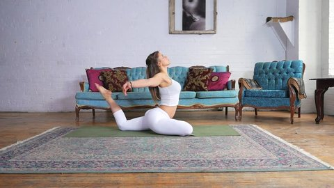 Young Attractive Female Doing A King Pigeon Pose On A Yoga Mat