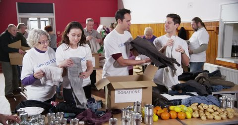 4k / Ultra HD version A mixed group of male and female charity workers are sorting through goods which have been donated by the people of their local community. In slow motion. Shot on RED Epic
