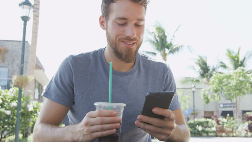 Young man using smartphone while sitting at sidewalk cafe. Smiling male is holding drink drinking iced coffee while text messaging on mobile cell smart phone. Handsome man is in casuals. | Shutterstock HD Video #14150939