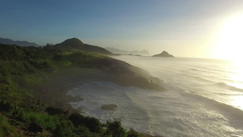 Drone view of a mythical scenery in a bucolic coast during sunset on a romantic morning in Rio de Janeiro. A classic road beside a calm sea with some beautiful waves ins a surf & sports paradise city