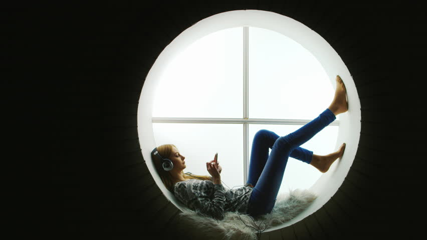 Attractive woman sitting at the round window, listening to music.