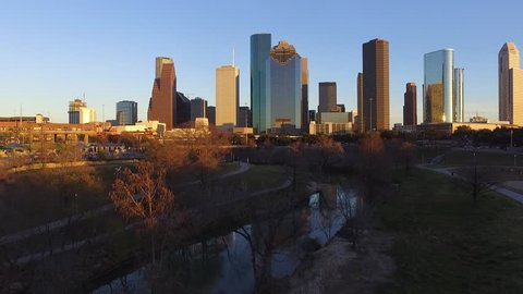 Fast ascending aerial footage of downtown and buffalo bayou at sunset on a warm, colorful autumn day. Shot rises and then sits still with view of rush hour traffic.