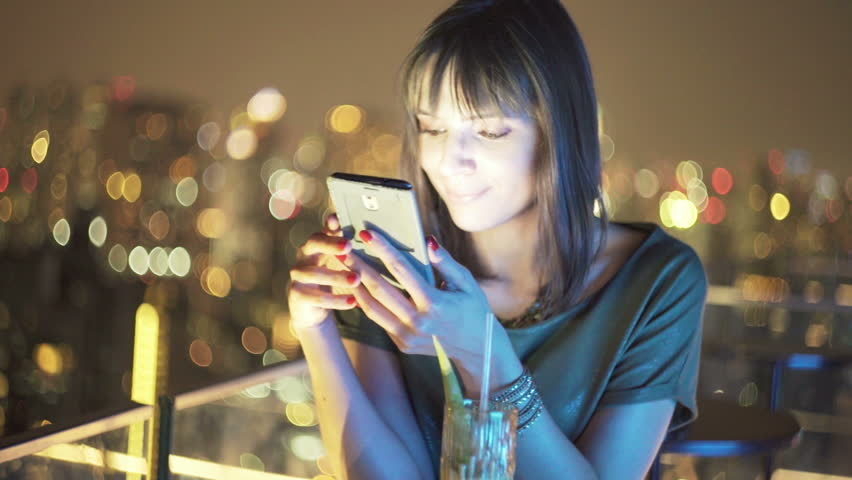 Young, pretty woman using smartphone in bar at night