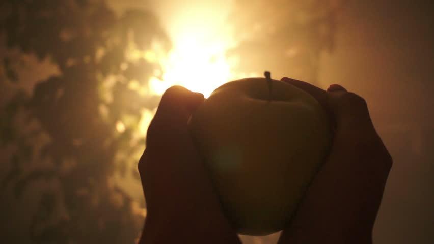 Eve's hands hold the forbidden fruit (an apple) in the garden of Eden.