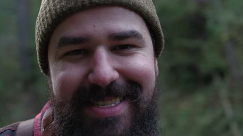 Portrait of a smiling lumberjack woodsman in flannel out in the forest.