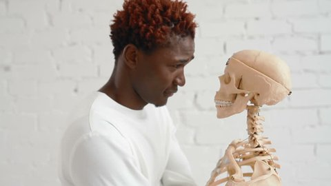 An insane black man wearing a straitjacket dance and looking at human skeleton stand