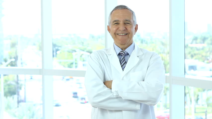 Senior male doctor walks into frame, crosses arms and nods, he is smiling
