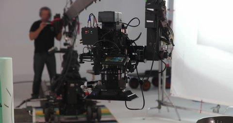 Camera jib operator moving Red Dragon upwards on professional production film set 4K Prores HQ