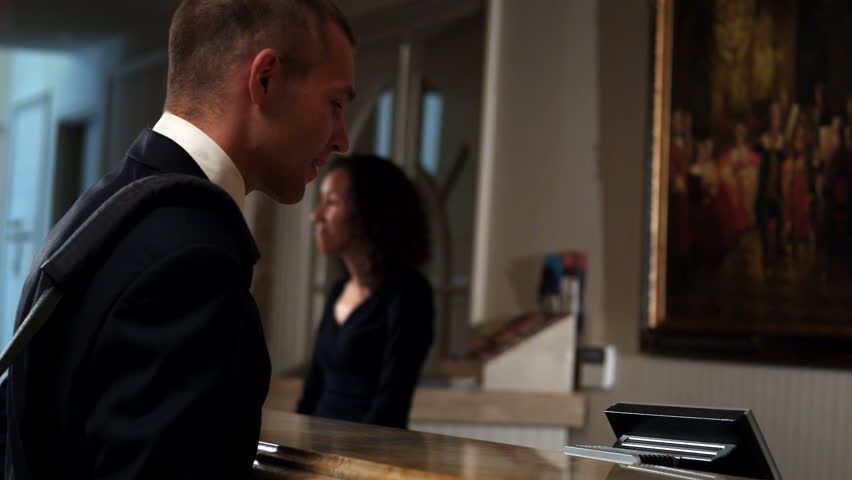 A young businessman flirts with the hotel staff as he checks in for the night.