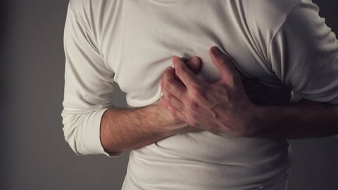 Man suffering from spasm or chest pain, having severe heart attack or painful cramps, pressing on chest with painful expression.