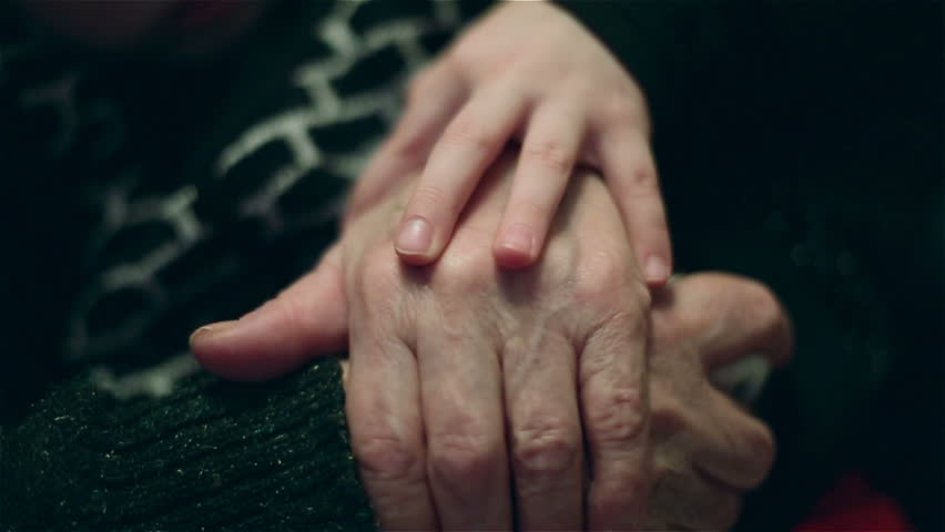 Hand of a little girl fondling old  hands of grandmother with love. Child is caring for grandmother.