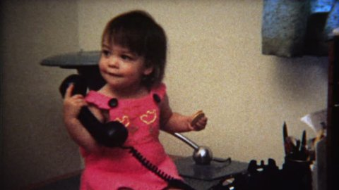 BOULDER, CO. 1971: Cute toddler girl playing with telephone on office desk.