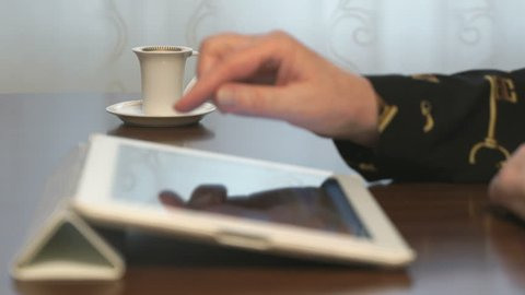 Woman works over documents using a digital tablet and drinks coffee