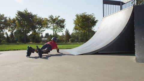 Boy Rollerblading at park, falling down
